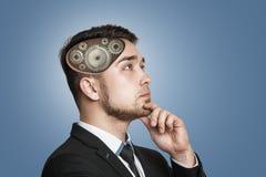 En ung allvarlig affärsman djupt i tanke med kugghjul inom hans huvud royaltyfri bild