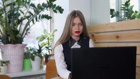 En ung allvarlig dam skrivar ut en ny artikel för tidskriften i kafé lager videofilmer