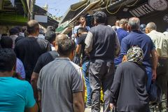 En ung arabisk man som försöker att sälja persikor till den övergående folkmassawhen arkivfoton