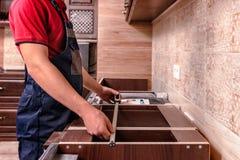 En ung arbetare monterar modernt träkökmöblemang fotografering för bildbyråer