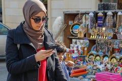 En ung Aresbaidan kvinna i hijab och exponeringsglas promenerar gatan av den gamla staden med traditionella azerbajdzjanska souve fotografering för bildbyråer