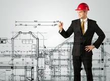 En ung arkitekt som drar ett husplan Arkivfoton