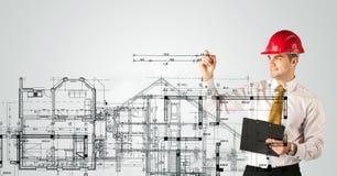 En ung arkitekt som drar ett husplan Royaltyfria Bilder