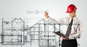 En ung arkitekt som drar ett husplan Arkivbilder
