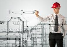En ung arkitekt som drar ett husplan Royaltyfri Bild