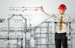 En ung arkitekt som drar ett husplan Arkivbild