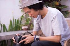 En ung asiatisk man för fokus med hatten och exponeringsglas som rymmer och granskar dslrkameran royaltyfri bild