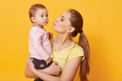 En ung att bry sig moder försöker att lugna ner hennes skriande dotter En reva ska köra ner gulliga baby'sens kind Ett besviket b fotografering för bildbyråer