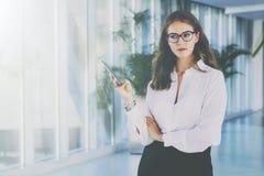 En ung attraktiv affärskvinna i exponeringsglas och en vit skjorta står i kontoret, genom att använda en smartphone arkivfoton