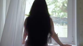 En ung attraktiv brunett med långt härligt hår öppnar gardinerna långsam rörelse stock video