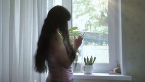 En ung attraktiv flicka med långt härligt hår står vid fönstret, och tala på telefonen, skriver sms långsamt stock video