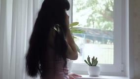 En ung attraktiv flicka med långt härligt hår står vid fönstret, och tala på telefonen, skriver sms långsamt lager videofilmer