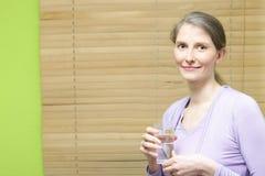 En ung attraktiv kvinna som rymmer ett exponeringsglas Arkivbild