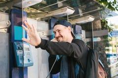 En ung attraktiv modern man talar på en payphone och välkomnanden med hans hand svart telefon för kommunikationsbegreppsmottagare Royaltyfri Foto