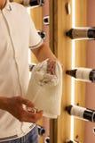 En ung bartender torkar handdukvinexponeringsglas på arbete i restaurangen på bakgrunden av flaskor av vin Royaltyfria Foton