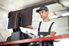 En ung blåögd mekaniker kontrollerar en bil på en bilservice genom att använda en dator arkivfoto