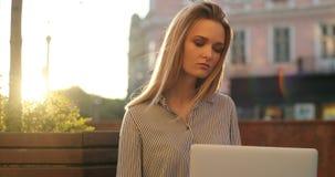 En ung blond affärsdam sitter på en bänk på en solig dag och arbetar på hennes bärbar dator, närbild stock video