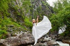 En ung blond flicka i ett elegant poserar drar upp en budoarklänning i bergen mot en vattenfall och stenar som lyfter hennes händ arkivfoto