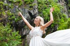 En ung blond flicka i ett elegant poserar drar upp en budoarklänning i bergen mot en vattenfall och stenar som lyfter hennes händ royaltyfri bild