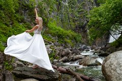 En ung blond flicka i ett elegant poserar drar upp en budoarklänning i bergen mot en vattenfall och stenar som lyfter hennes händ arkivbild