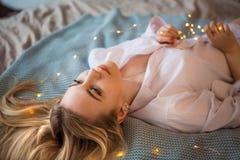 En ung blond flicka i en lång vit manlig skjorta som ligger på sängen som kastar hennes hår på filten royaltyfria bilder