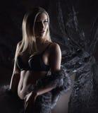 En ung blond kvinna i mörk damunderkläder och päls Royaltyfri Bild