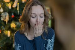 En ung blond kvinna mottog en gåva för jul på julgranen och var mycket förvånad vid överraskningen royaltyfria bilder