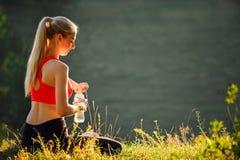 En ung blondin i en röd överkant och svarta flåsanden sitter på gräset i natur En sportig kvinna rymmer en flaska av vatten Royaltyfri Fotografi