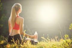 En ung blondin i en röd överkant och svarta flåsanden sitter på gräset i natur En sportig kvinna rymmer en flaska av vatten Royaltyfria Foton