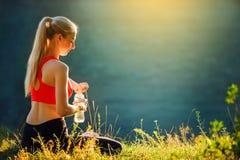 En ung blondin i en röd överkant och svarta flåsanden sitter på gräset i natur En sportig kvinna rymmer en flaska av vatten Royaltyfri Bild
