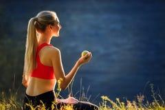 En ung blondin i en röd överkant och svarta flåsanden sitter på gräset i natur En sportig kvinna rymmer ett grönt äpple i henne h Arkivbilder