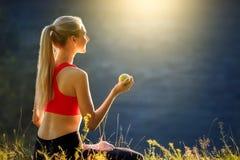 En ung blondin i en röd överkant och svarta flåsanden sitter på gräset i natur En sportig kvinna rymmer ett grönt äpple i henne h Royaltyfri Foto