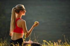 En ung blondin i en röd överkant och svarta flåsanden sitter på gräset i natur En sportig kvinna rymmer ett grönt äpple i henne h Royaltyfria Bilder