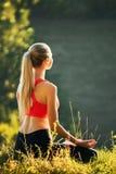 En ung blondin i en röd överkant sitter på gräset för kondition i natur En idrottskvinna förbereder sig för gymnastik Royaltyfri Fotografi