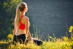 En ung blondin i en röd överkant sitter på gräset för kondition i natur En idrottskvinna förbereder sig för gymnastik Royaltyfria Bilder