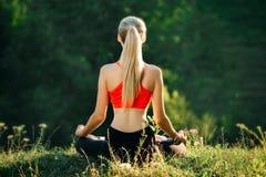 En ung blondin i en röd överkant sitter på gräset för kondition i natur En idrottskvinna förbereder sig för gymnastik Arkivfoto