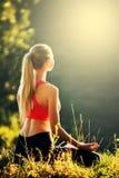 En ung blondin i en röd överkant sitter på gräset för kondition i natur En idrottskvinna förbereder sig för gymnastik Arkivbild