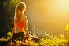 En ung blondin i en röd överkant sitter på gräset för kondition i natur En idrottskvinna förbereder sig för gymnastik Royaltyfri Bild