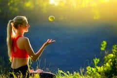 En ung blondin i en röd överkant sitter på gräset i natur En sportig kvinna kastar håll ett grönt äpple i henne händer Arkivfoton