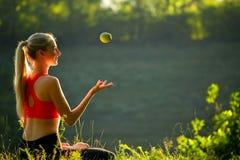 En ung blondin i en röd överkant sitter på gräset i natur En sportig kvinna kastar håll ett grönt äpple i henne händer Royaltyfria Foton