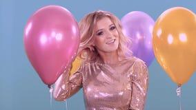 En ung blondin i en härlig klänning mot bakgrunden av ballonger jublar på hennes ferie, födelsedag arkivfilmer