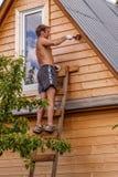En ung bonde är träbad för täckande abc-bokvägg Arkivfoton