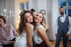 En ung brud och hennes kvinnliga vän som poserar på ett gifta sig mottagande, dans arkivfoto