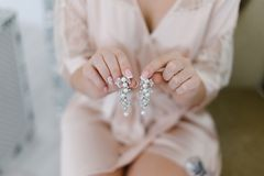 En ung brud rymmer örhängen i hennes händer royaltyfri bild