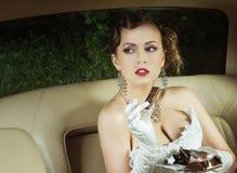 En ung brud som poserar i en bil arkivfoto