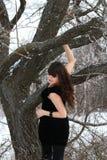 En ung brunett i en svart klänning i skogen Arkivfoto