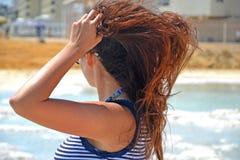 En ung brunett i en randig T-tröja solbadar på kusterna av det döda havet Flickan vände hennes baksida royaltyfria bilder