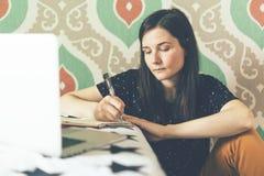 En ung brunettflicka gör anmärkningar i en anteckningsbok arkivbilder