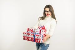 En ung brunettkvinna i exponeringsglas och en hållande julklapp för vit tröja Arkivfoto