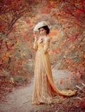 En ung brunettkvinna med ett elegant, frisyr i en hatt med strass befjädrar Damen i en gul tappningklänning går royaltyfria bilder